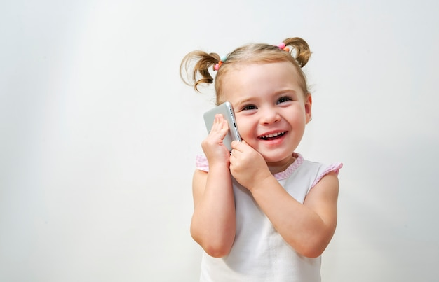 Portrait of the little girl's positive that talking on a phone Premium Photo