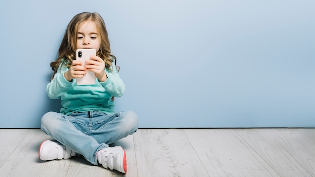 Portrait of a little girl sitting on hardwood floor looking at smartphone Free Photo