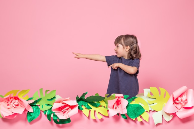 Portrait of a little girl on a summer pink background Free Photo