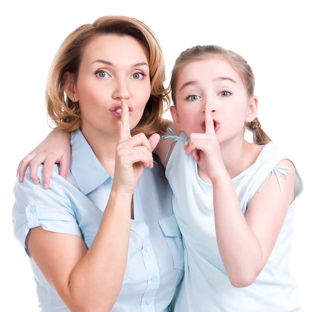 Ritratto di una bambina che dice a sua madre un colpo segreto in studio Foto Gratuite
