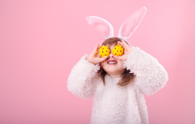 Portrait of a little girl with bunny ears and easter eggs Free Photo