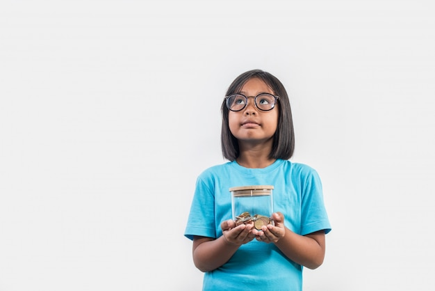 Portrait of little girl with her savings in studio shot Free Photo