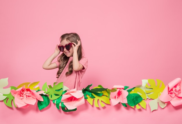 Portrait of a little girl with sunglasses on a pink background Free Photo