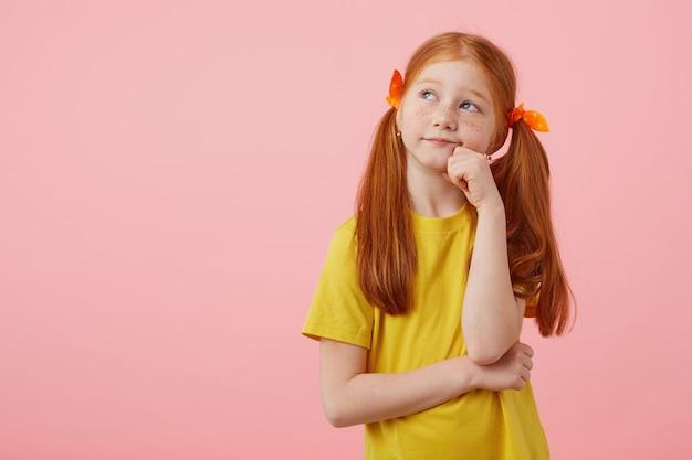 Портрет маленькой задумчивой веснушчатой рыжеволосой девушки с двумя хвостами, смотрит в сторону, трогает щеки, носит желтую футболку, стоит на розовом фоне. Бесплатные Фотографии