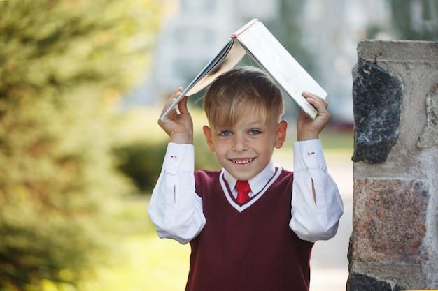 Portrait little schoolboy on nature background. Premium Photo