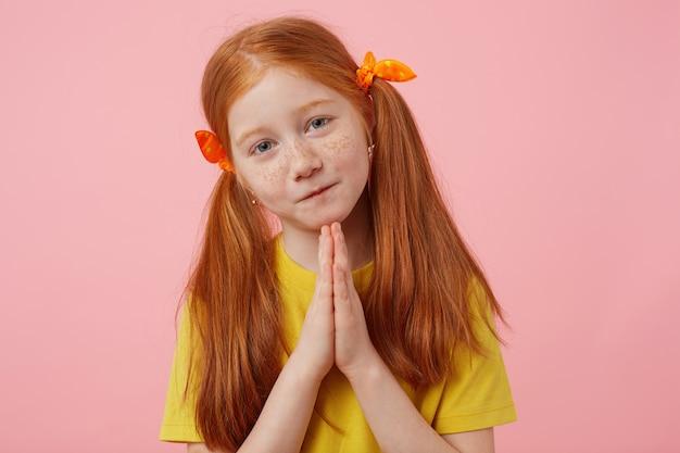 Портрет маленькой грустной рыжеволосой девушки с веснушками с двумя хвостами, смотрит в камеру и сложенные вместе руки, жест preyer, носит желтую футболку, стоит на розовом фоне. Бесплатные Фотографии