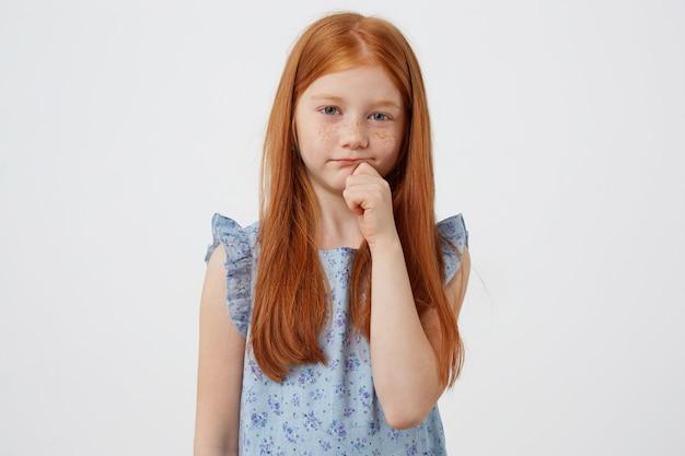 Ritratto di piccola ragazza dai capelli rossi lentiggini infelici, guarda tristemente la telecamera, indossa un abito blu, si trova su sfondo bianco. Foto Gratuite