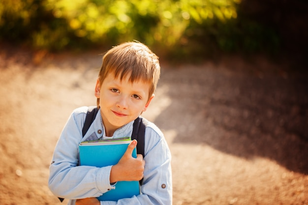 Portrait littleschoolboy with backpack and books. outdoors Premium Photo