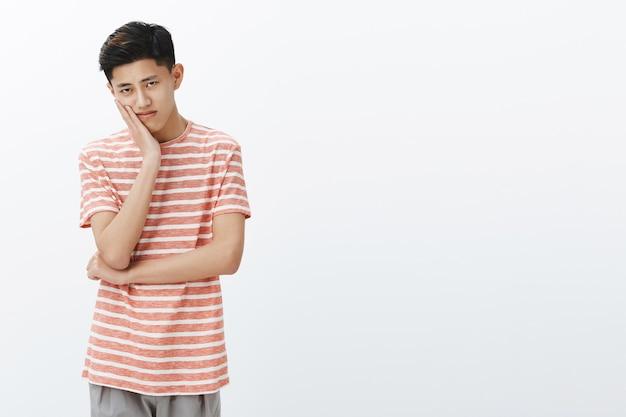 Ritratto di giovane studente asiatico maschio sconvolto e annoiato solitario con taglio di capelli corto scuro che si appoggia la testa sul palmo guardando con sguardo cupo e indifferente guardando film noioso sul lato sinistro dello spazio della copia Foto Gratuite