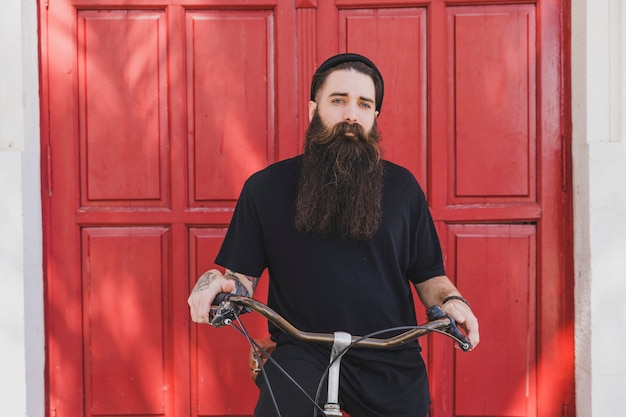 Portrait of a long bearded young man siting on bicycle looking at camera Free Photo