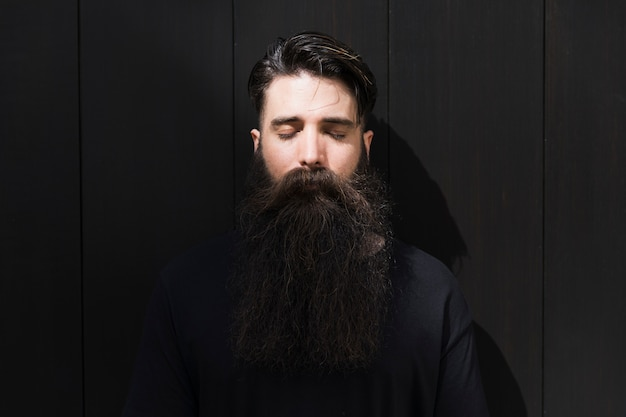 Portrait of a long bearded young man with eye closed in front of black brick wall Free Photo