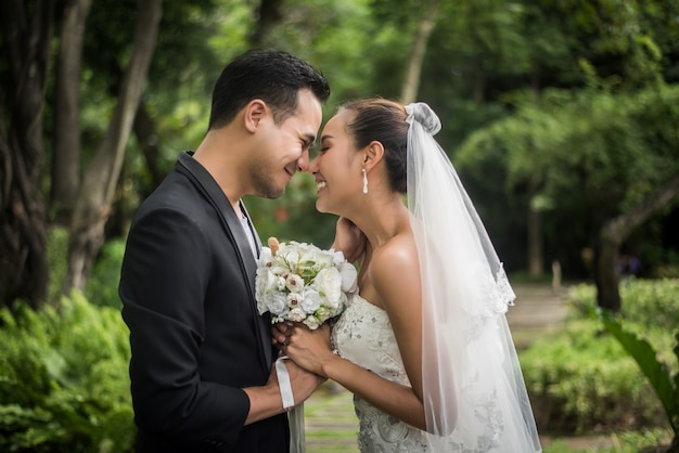 Portrait of love wedding day groom give flowers bouquet to his bride. Free Photo