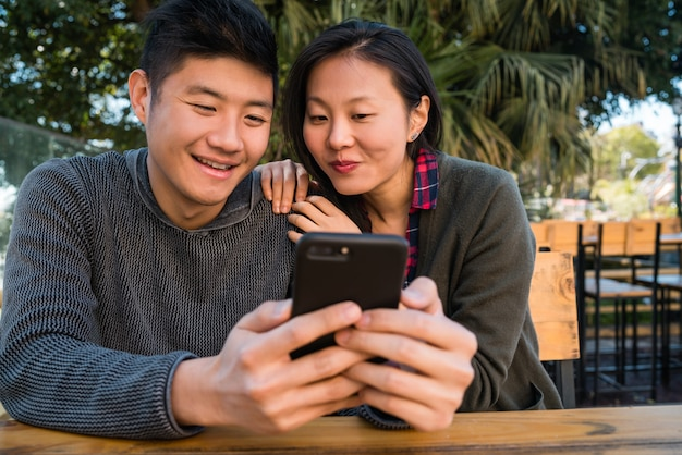 Portrait of lovely asian couple looking at the mobile phone while sitting and spending time at the coffee shop. Free Photo