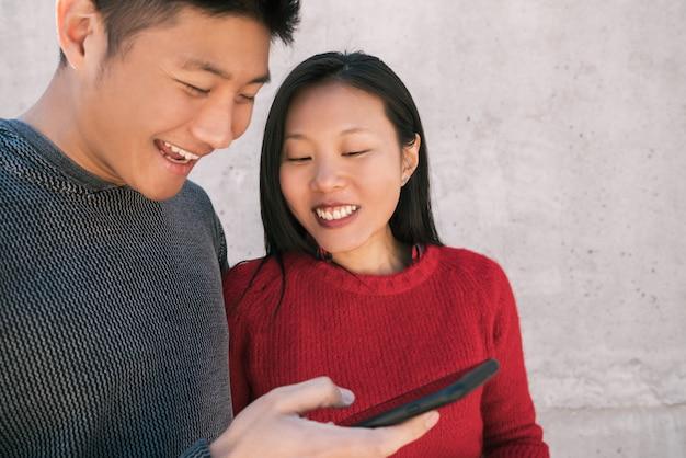 Ritratto di belle coppie asiatiche guardando il telefono cellulare mentre trascorrono del buon tempo insieme. Foto Gratuite