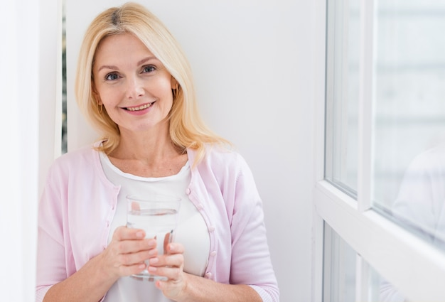 Portrait of lovely mature woman holding a glass of water Free Photo