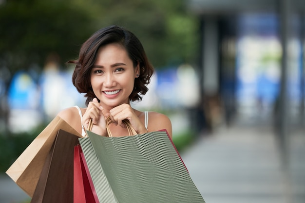 Portrait of lovely shopaholic girl standing with a stack of shop bags outdoors Free Photo