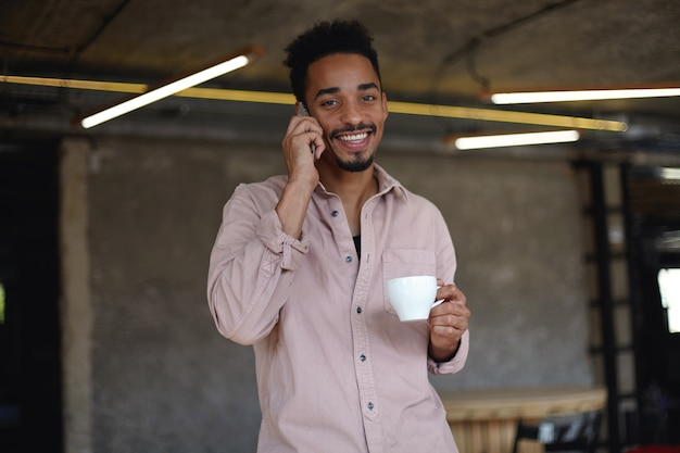 Ritratto di adorabile giovane uomo barbuto con la pelle scura che guarda allegramente con un ampio sorriso affascinante, bere il tè e fare chiamate con il suo telefono cellulare, vestito con una camicia beige Foto Gratuite