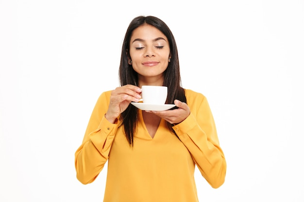 Ritratto di una giovane donna adorabile che odora la tazza di tè Foto Gratuite