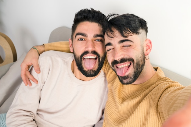 Portrait of loving homosexual couple sticking out their tongue out Free Photo