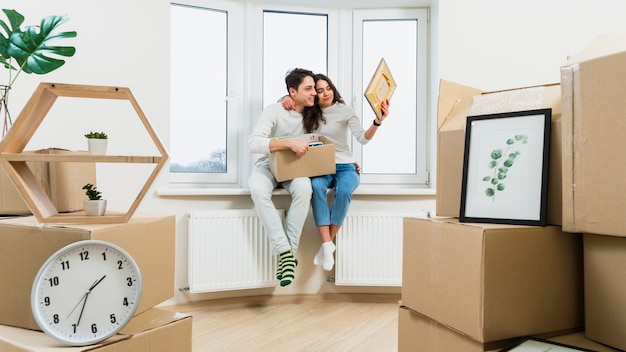 Portrait of loving young couple sitting on window sill in new apartment looking at picture frame Free Photo