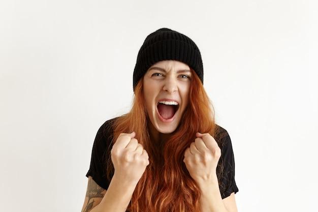 Ritratto di donna giovane rossa pazza e furiosa in cappello hipster che esprime rabbia e rabbia Foto Gratuite