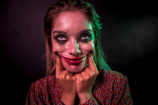 Portrait of a make-up clown horror character smiling Free Photo