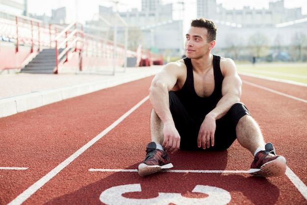 Portrait of male athlete relaxing on the red race track Free Photo