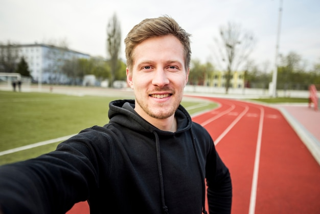 Portrait of male athlete taking selfie on mobile phone on the red race track Free Photo