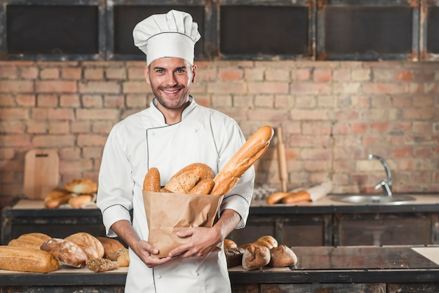 Portrait of male baker holding loaf of breads in paper bag Free Photo