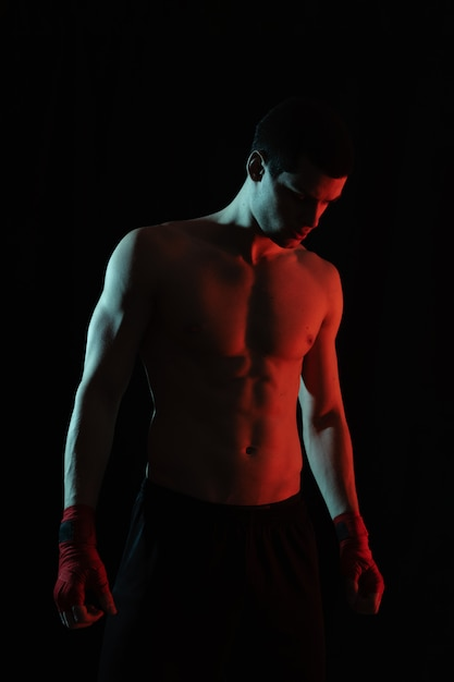 Portrait of male boxer posing in red and white light Free Photo