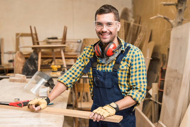 Portrait of a male carpenter holding wooden plank on workbench in the workshop Free Photo
