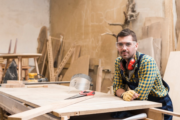 Portrait of a male carpenter leaning on workbench in the workshop Free Photo