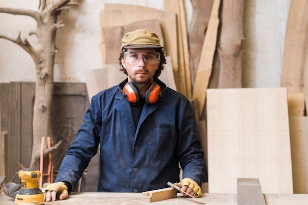Portrait of a male carpenter wearing safety glasses standing behind the workbench Free Photo