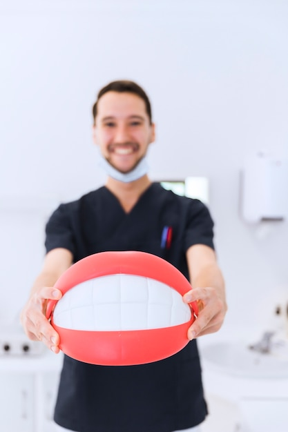 Portrait of male dentist showing teeth model at dental clinic Free Photo