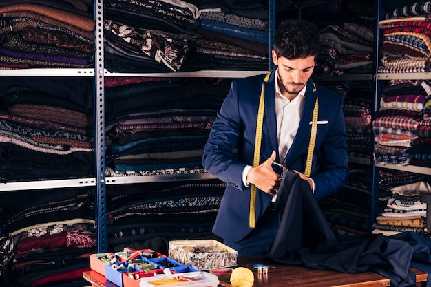 Portrait of a male fashion designer cutting the fabric with scissor in his workshop Free Photo