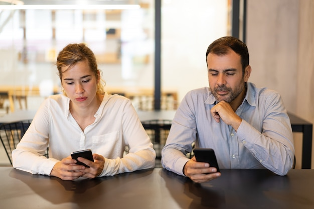 Portrait of male and female colleagues using phones at cafe Free Photo