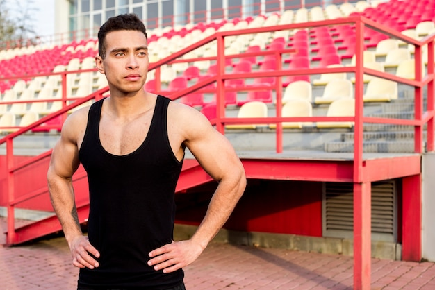 Portrait of a male fitness young man standing in front of bleacher Free Photo