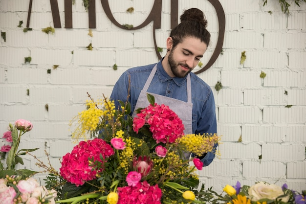 Portrait of male florist arranging the mimosa and hydrangea macrophylla flower creating bouquet Free Photo