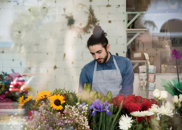 Portrait of a male florist standing behind the colorful flowers in the flower shop Free Photo