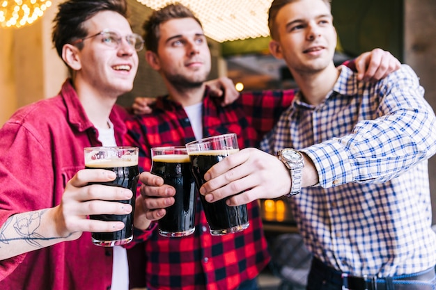 Portrait of male friend clinking glasses with beer in pub Free Photo