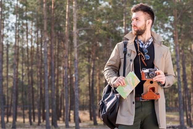 Portrait of a male hiker with camera and map standing in the forest Free Photo