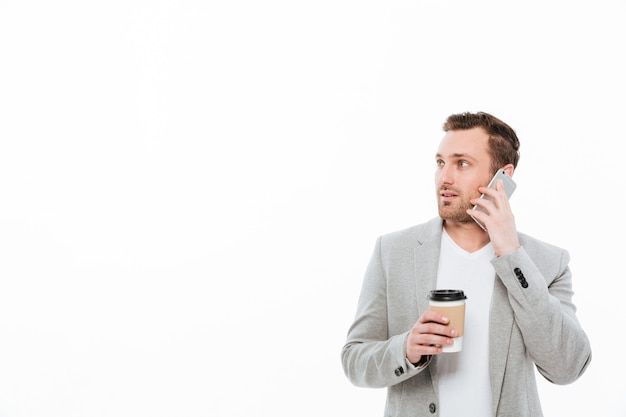 Portrait of male office worker drinking takeaway coffee while having pleasant mobile conversation on cellphone and looking aside, over white wall Free Photo