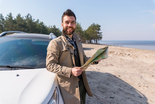 Portrait of a male traveler standing near the car holding map in hand looking at camera Free Photo