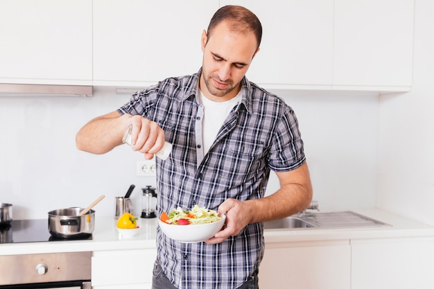 Portrait of a man adding spices in salad bowl Free Photo
