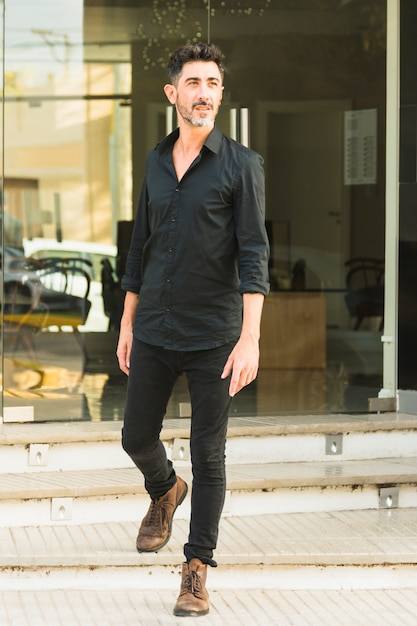 Portrait of a man in black shirt and jeans standing in front of glass door Free Photo
