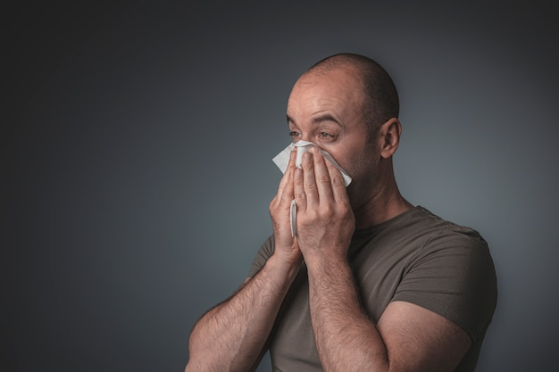 Portrait of a man blowing his nose with a tissue Premium Photo