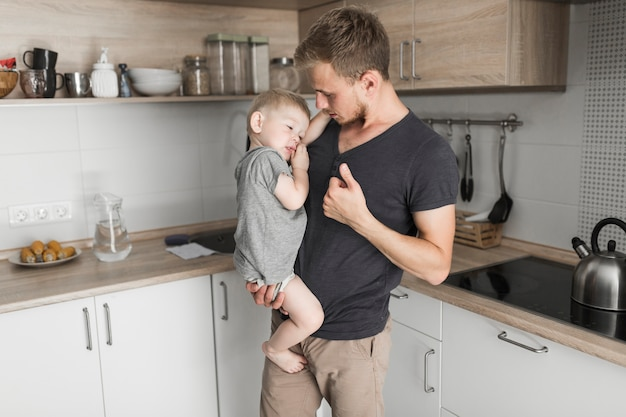 Portrait of a man carrying his little son standing in the kitchen gesturing Free Photo