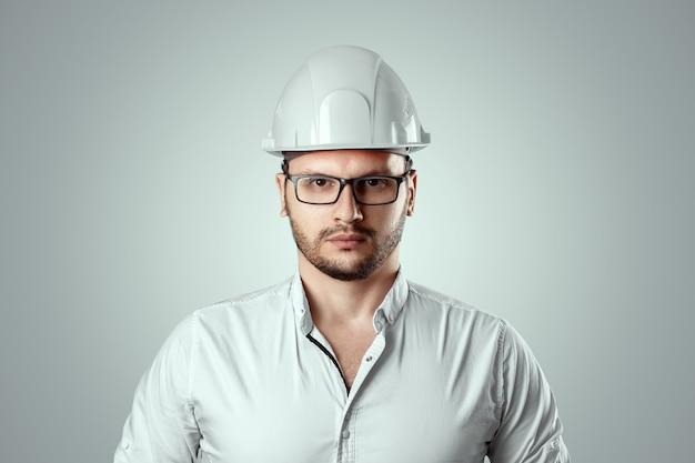 Portrait of a man in a construction white helmet. concept architecture, construction, engineering, design, repair. copy space Premium Photo