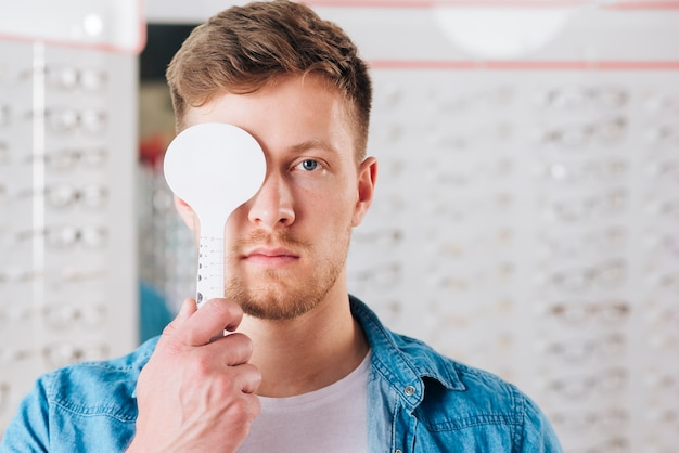 Portrait of man doing test of eye vision Free Photo