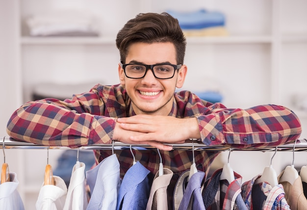 Portrait of man in glasses leaning on rack with clothes. Premium Photo